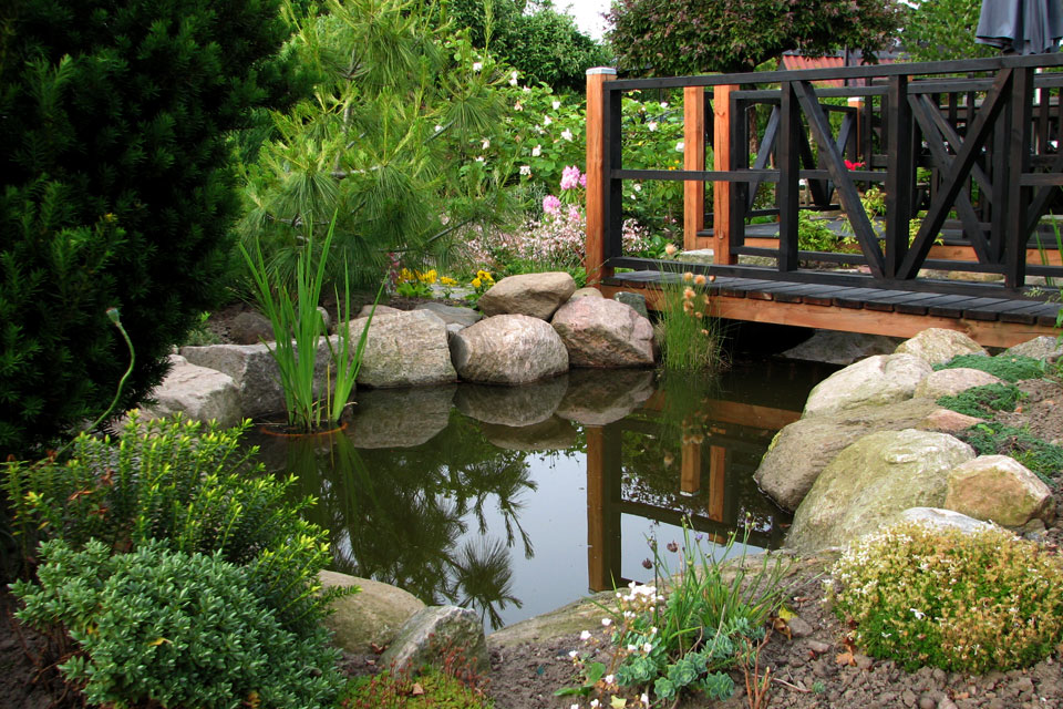 Большой и глубокий водоем, через который перекинут мостик - Сад Сусанне Расмуссен