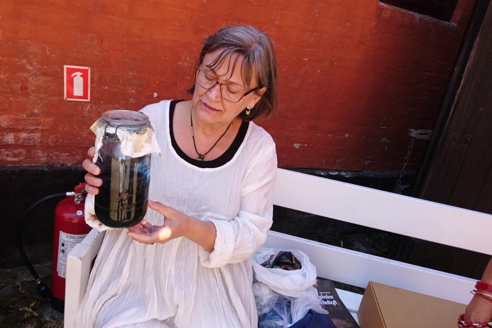 Сотрудница музея демонстрирует кубовый раствор индиго