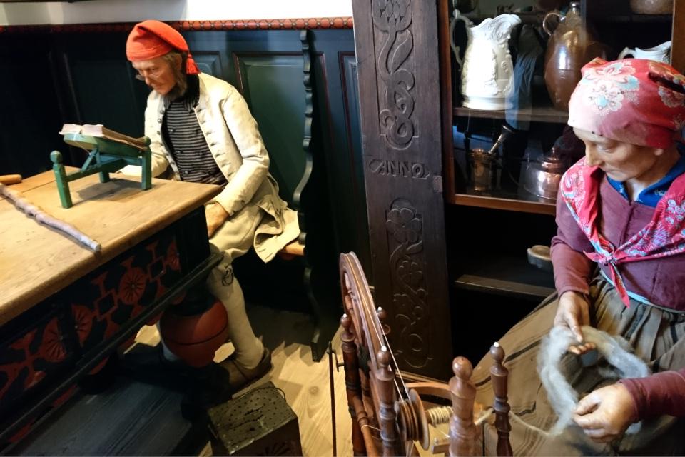 Экспозиция интерьера жилого дома времен 17 столетия с женщиной-прялкой.