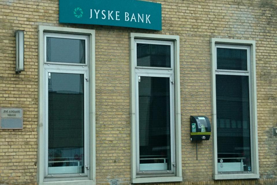 Дефибриллятор (АНД) в защитном корпусе на наружной стене здания банка, Дания