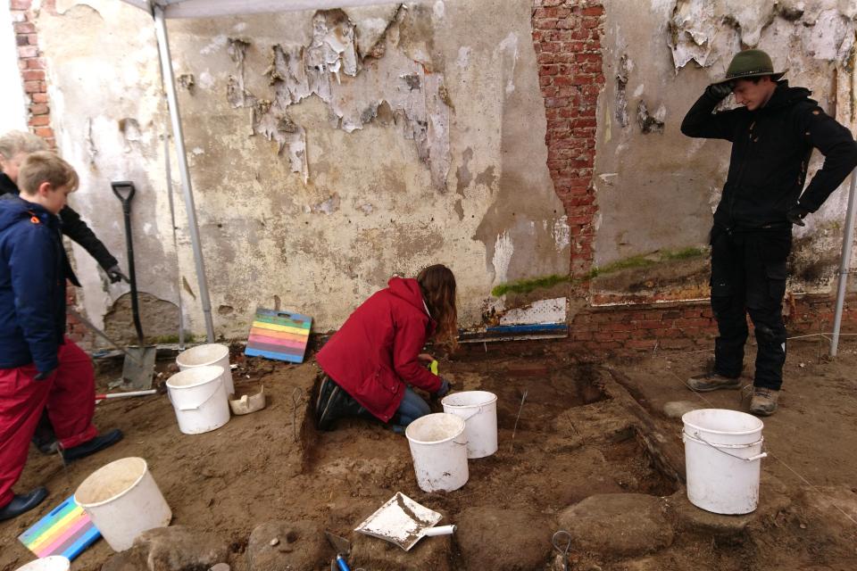 Добровольцам демонстрируются методы раскопок фундамента
