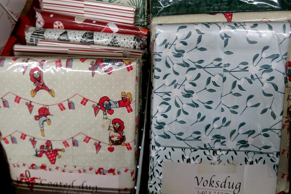 Скатерть с изображением омелы предлагается в супермаркете перед Рождеством.