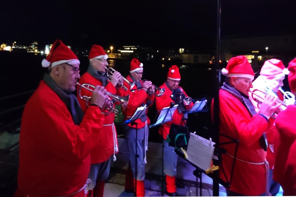 Оркестр с музыкантами, одетых в костюмы рождественских ниссе