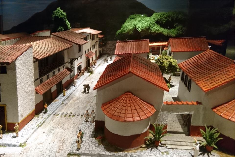 Дорога с переходами из камней возле домов на макете построек г. Помпеи