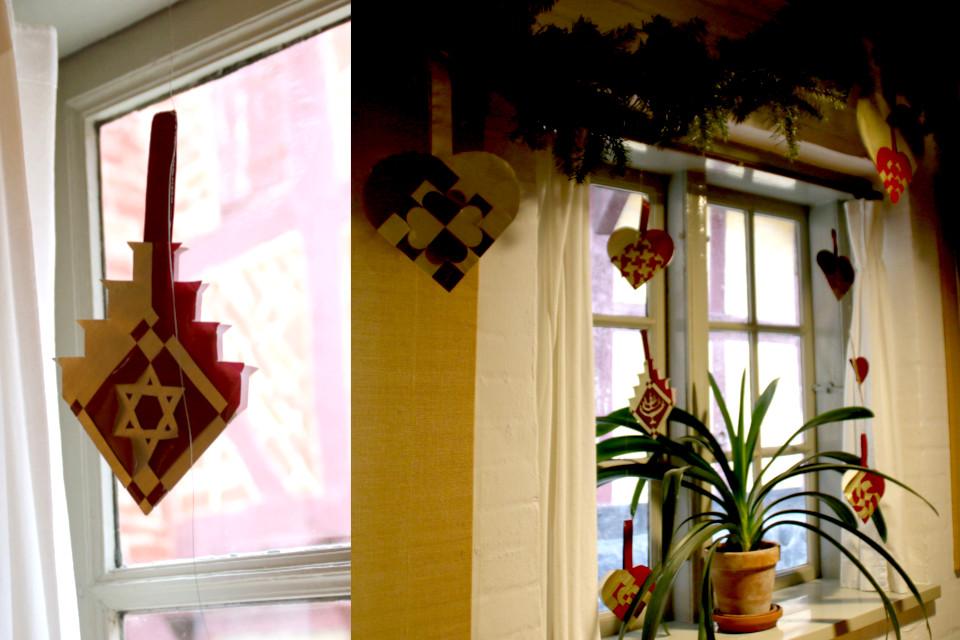 Разные формы и узоры плетеных сердечек на окнах рождественского зала